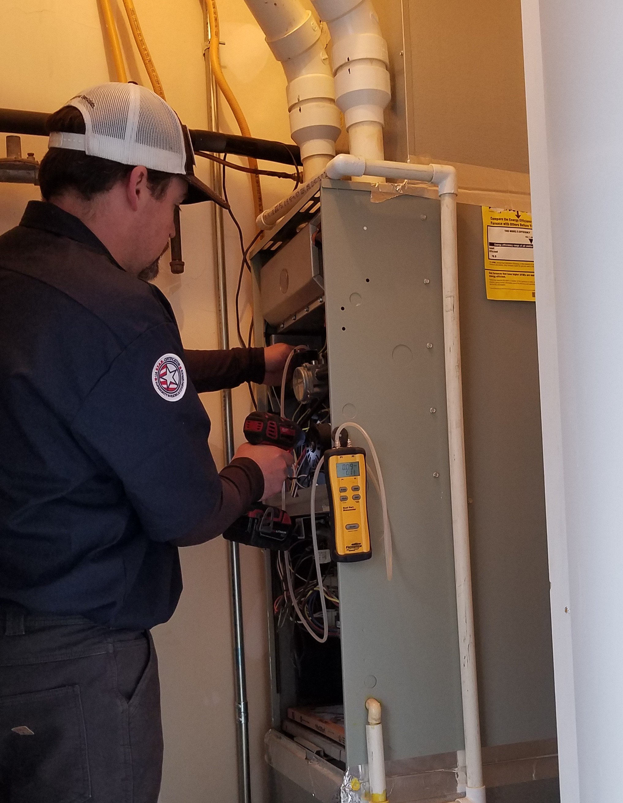 HVAC Technician performing maintenance on a gas furnace